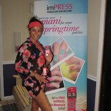Peer to peer marketing: imPress brand ambassador poses with KISS press-on manicures banner