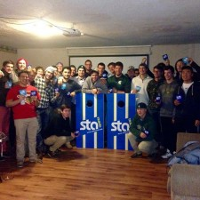 STA Travel at fraternity with corn hole game and beer coozies