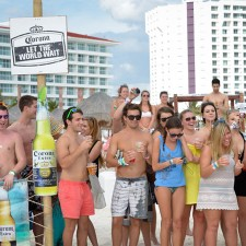 Experiential marketing: college co-eds enjoy Corona, while surrounded by signs & banners, on the beach in Cancun